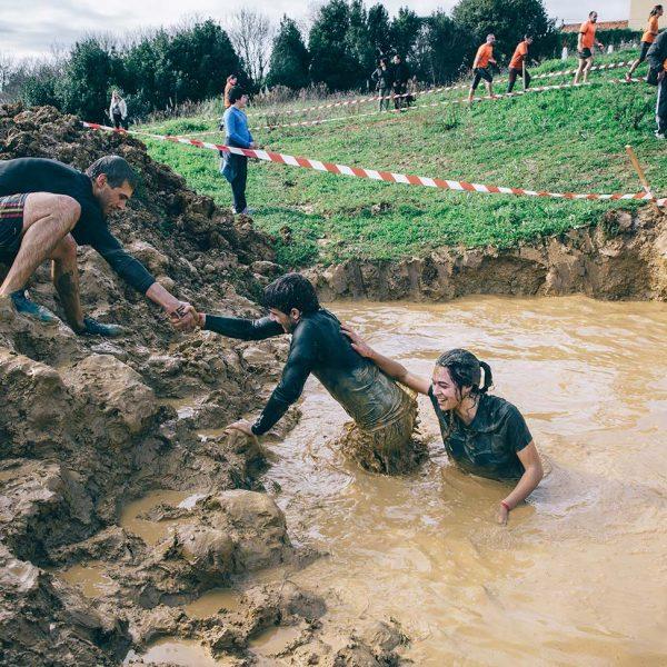 bigstock-Team-helping-to-cross-mud-pit--116872709